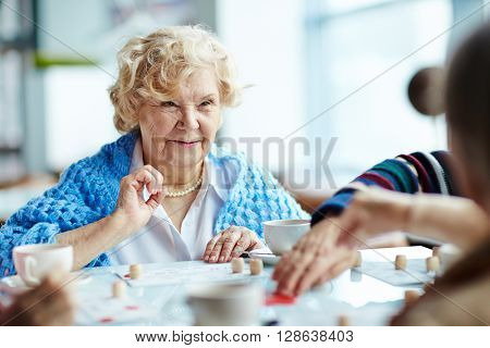 Senior woman playing lotto with friends