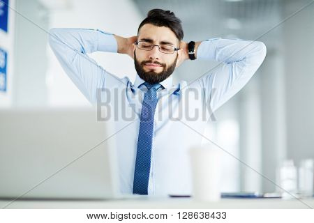 Relaxed businessman sitting with his hands behind head