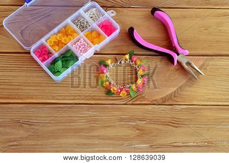 Bright beautiful handmade bracelet. Pliers. Box with beads, plastic flowers and accessories for handmade jewelry on old wooden background. Copy space for text. Top view