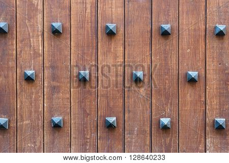 Old medieval time wall with decorative rivets wooden plank background