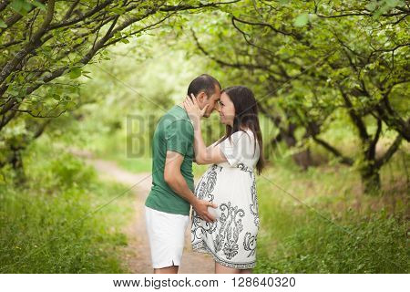 Happy Couple Waiting For Baby. Man Touches Pregnant Belly, Pregnant Woman Hugs Him In Garden In Summ