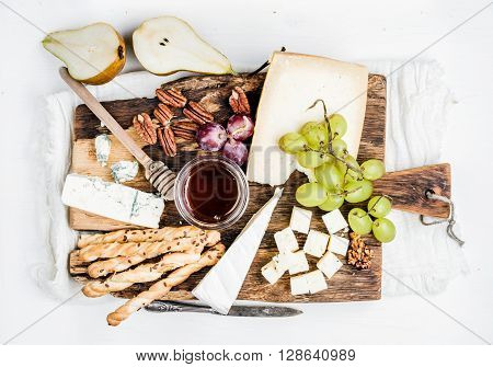 Cheese appetizer set. Various types of cheese, honey, grapes, pear, nuts and bread grissini sticks on rustic wooden board over white background, top view, horizontal