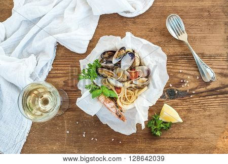 Seafood pasta. Spaghetti with clams and shrimps in bowl, glass of white wine over rustic wood background, top view