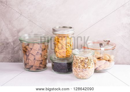 Assortment of cereals, flakes, nuts and berries in storage glass jars over kitchen table. Homemade granola bar ingredients