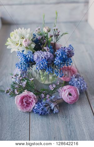 on a wooden background bouquet of muscari and other flowers in a vase
