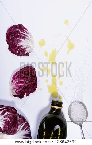 Radicchio red salad leaves with olive oil and sea salt. Top View, white background.