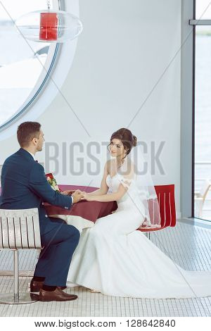Wedding couple in love. Beautiful bride in white dress and veil and brides bouquet with handsome groom in blue suit sitting in cafe. Full lenght portrait of man and girl. Concept of wedding celebration in vacation