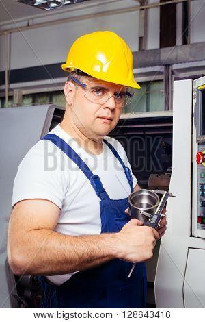Factory man worker measuring steel detail with digital Vernier Caliper at workshop