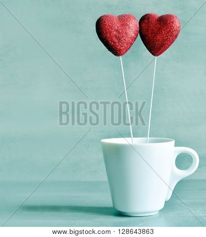 Two candy hearts in the white cup for Valentine's Day with blue background.