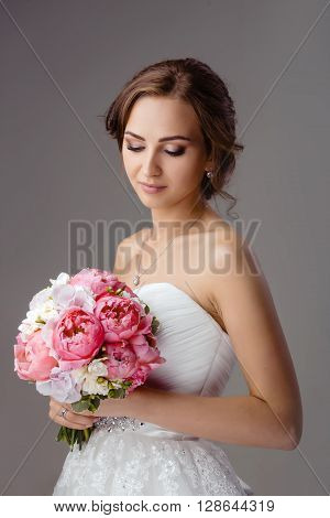 Beautiful bride with fashion wedding hairstyle on gray background. Closeup portrait of young sensual gorgeous bride with wedding bouquet. Studio shot