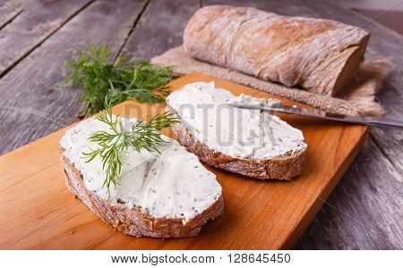 A slice of freshly baked ciabatta bread and healthy low fat cream cheese with dill and fresh green dill on wooden board.