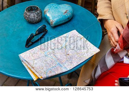 A tourist from Europe sitting in the cafe for a vintage blue table and studying the city map. On the table sunglasse, map,  candlestick
