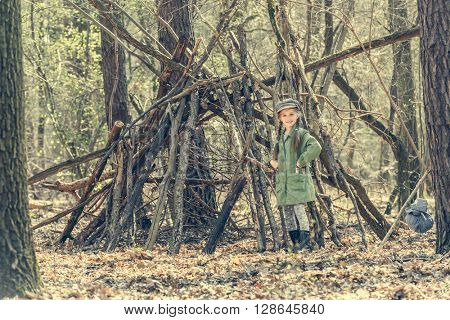 ittle cute girl builds a hut in the woods