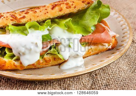 Tasty ham sandwich with salad leaf cheese and cucumber sauce in a cheese bread homemade on breakfast.
