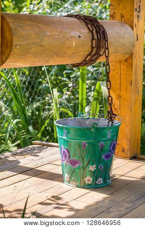painted metal bucket on a wooden village well
