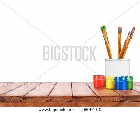 set of different brushes pencils palette knife in the bank next to the oil paints on a wooden table on a white background