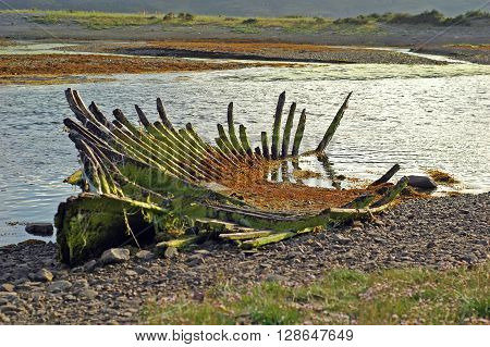 Rotten boat on the banks of a river inlet