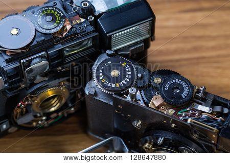 Disassembled broken vintage film camera on wooden table
