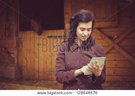 Female working on digital tablet in front of the stable