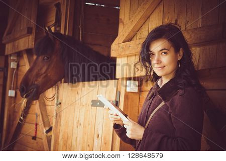 Female working on digital tablet next to the horse stable