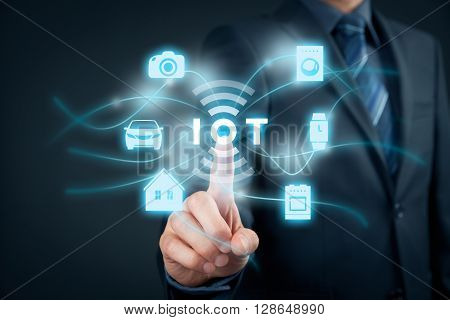 Internet of things (IoT) concept. Businessman click on IoT symbol connected with icons of typical IoT - intelligent house car camera watch washing machine and cooker.