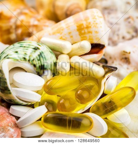 Mixed natural food supplement pills on the beautiful seashells background omega 3 calcium glucosamine capsules