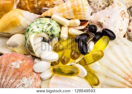 Mixed natural food supplement pills on the beautiful seashells background omega 3 calcium carotene glucosamine capsules