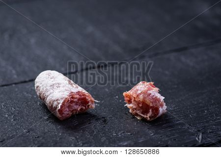 Bitten Off Pieces Of Sausage On Wooden Table