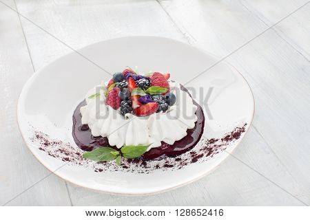 Meringue with berries and whipped cream on a wooden table with tea and kitchenware foroforovoy