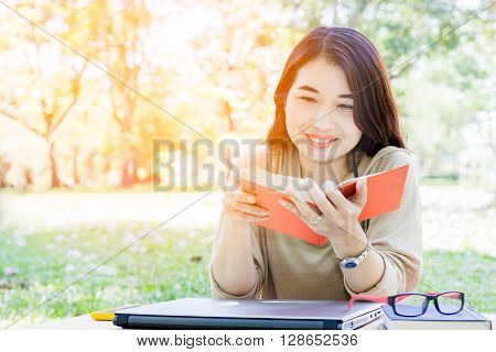 Asian young lady read book at outdoor in park.