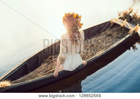Young sexy woman on boat at sunset. The girl has a flower wreath on her head, relaxing and seiling on river. Fantasy art photography. Concept of female beauty, rest in the nature, and water travel.