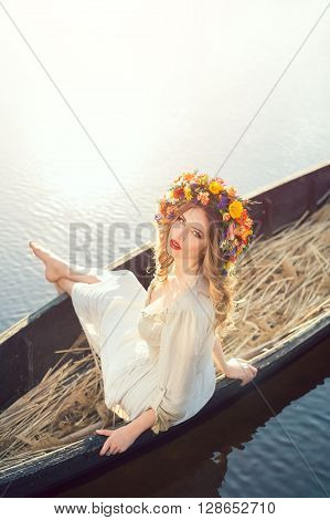 Young sexy woman on boat at sunset. The girl has a flower wreath on her head, relaxing and seiling on river. Beautiful body and face. Fantasy art photography. Concept of female beauty, rest in the nature, and water travel