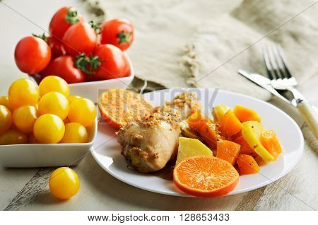 chicken drumstick cooked in spices with vegetables in the plate on the white wooden table. horizontal format