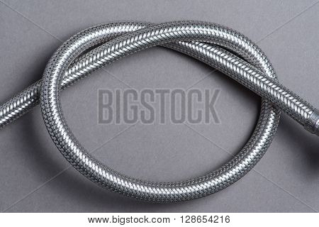 Braided Stainless Steel Water Hose Over Grey Background