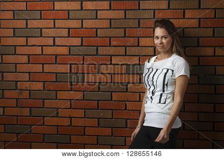 twenty something girl leaning against wall against brick wall