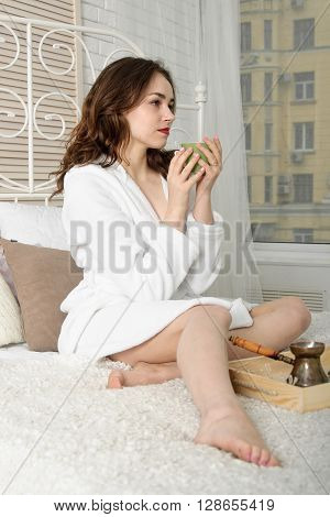 Girl Drinking Coffee While Lying In Bed.