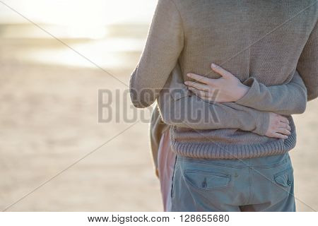 woman's hand tenderly hugging a man in a gray sweater