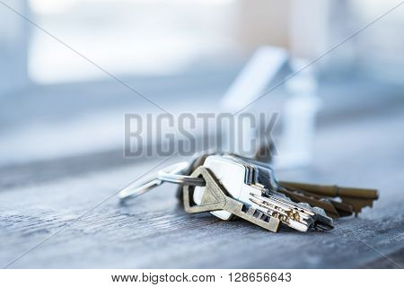 A Bunch Of Old Worn Keys With Metal House On The Wooden Surface