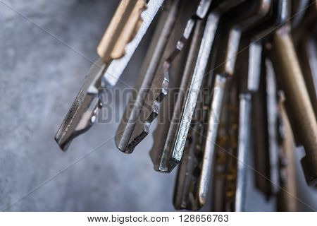 A Bunch Of Old Worn Keys On The Grey Concrete Wall