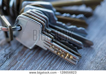 A Bunch Of Old Worn Keys On The Wooden Surface