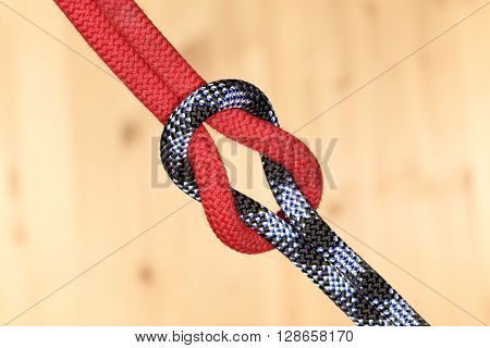 two ropes are connected with wooden background
