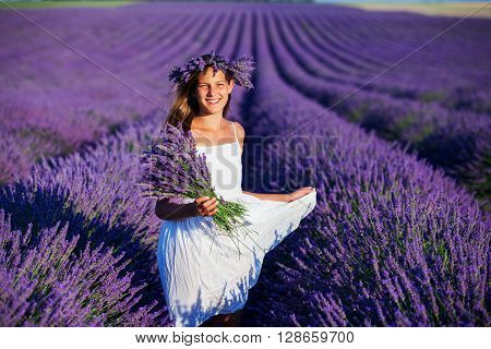 Beautiful young girl with bouquet in the lavander fields in Valensole. Provence, France.