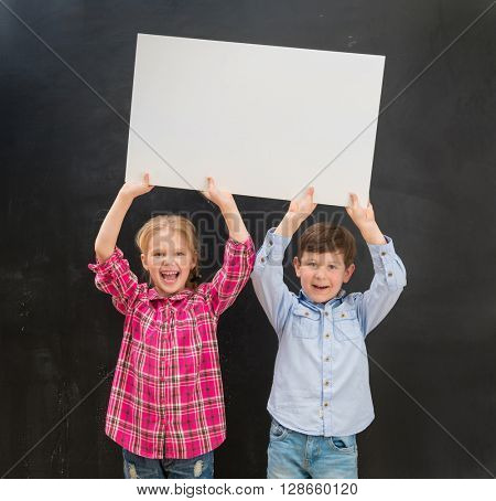 two little laughing children keeping blank paper sheet above their heads