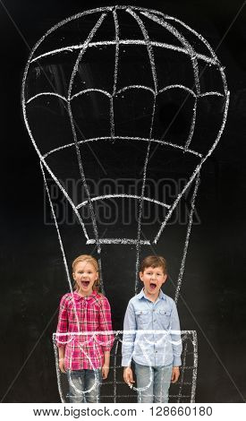 two laughing little schoolchildren flying on imaginary drawn air baloon on the blackboard