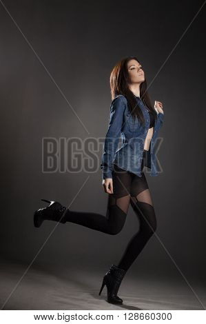 Brunette woman in pantyhose and jean jacket on a gray background.