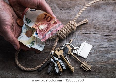 Hands Holding Money With Hangman's Noose, Keys And Money On Brown Wooden Surface