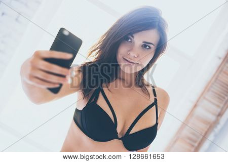 Selfie in the morning. Beautiful young woman in black lingerie making selfie while standing in front of window