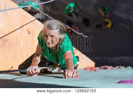 Elderly Female Makes Hard Move on Outdoor Climbing Wall Sporty Clothing on Fitness Training Intense but Positive Face Using Rope and Belaying Gear