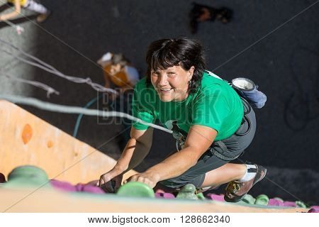 Portrait of Cute Adult Female Climber Moving Up on Sport Training Course in Outdoor Climb Gym Using Rope and Belaying Gear