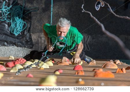 Aged Male Climber Moving Up on Outdoor Climbing Wall on Veterans Extreme Sport Competitions